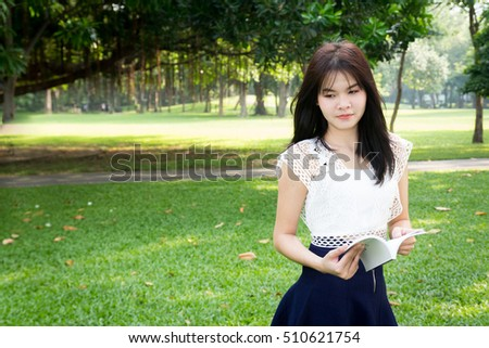 Photo of Young woman reading a book in garden