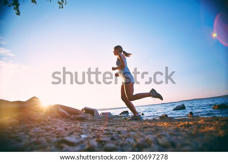 Photo of young woman running on the beach at dawn