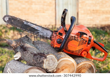 Photo orange chainsaw on heap firewood outdoors - stock photo