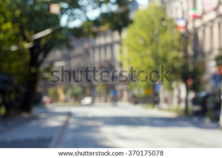 Photo out of focus sunny street in Europe. The road through town with many houses and trees. - stock photo