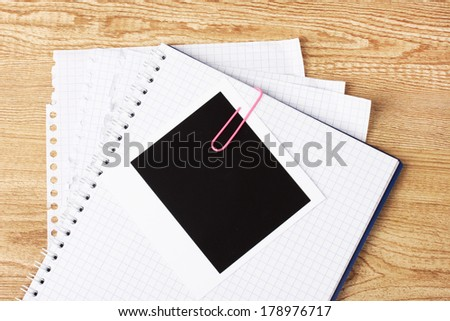 Photo paper and notebook on wooden background