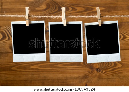 Photo paper attach to rope with clothes pins on wooden background  - stock photo