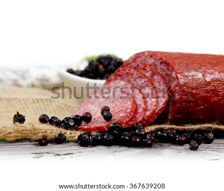 Photo salami with herbs and spice on wooden board - stock photo