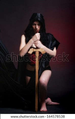 photo session in studio of the young girl in style art with an unusual makeup a girl in cloak and sword
