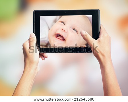 photo shooting on tablet pc a newborn baby - stock photo