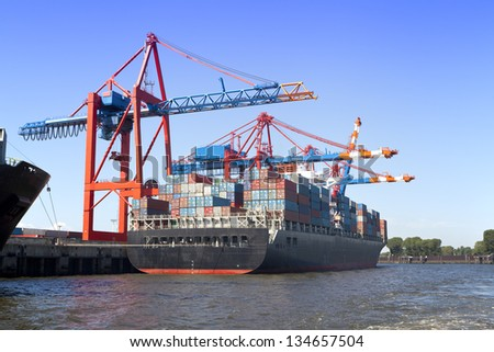 Photo shows a Container Terminal at the harbor in Hamburg, Germany. Container Terminal with a hugh Container Ship in front. - stock photo