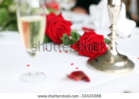 Photo shows a nice red rose on a wedding decorated table with a glass of sparkling wine and some small hearts