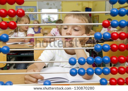 Photo shows a school boy in a math lesson. He is bored. - stock photo