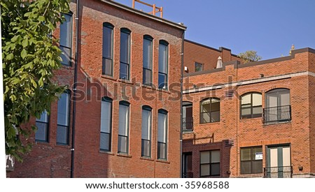 Photo shows an old style brick buildings of a cityscape with bright blue sky and old town charm.