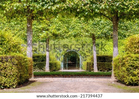 Photo shows French green garden with flowers and monuments.