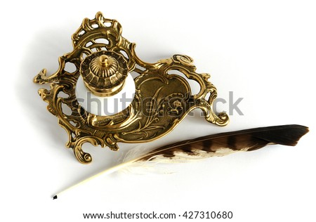 Photo shows Ornate antique brass inkwell with feather - stock photo