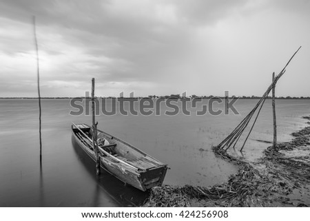 Photo small fishing boat tied to the shore. In the early rain that shows the movement of water and clouds.