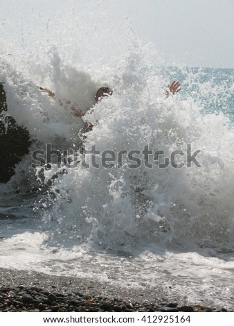 photo splashes of the waves. a man stands holding up my hands in sea foam