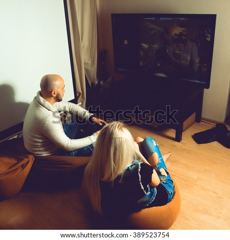 Photo square of couple having fun and playing computer games on tv. concept of leisure entertainment and fun - stock photo