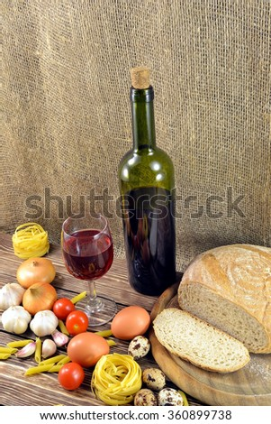 Photo still-life of standing on the table a bottle of red wine and wine glass pasta with bread and vegetables for dinner - stock photo