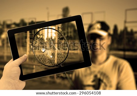 Photo tablet PC in hand with torn tennis badminton racket with stuck shuttlecock inside during play match - stock photo