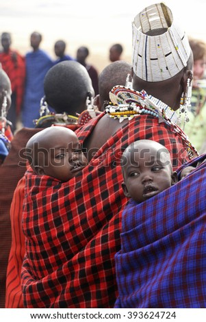 Photo taken at Nogorongoro, Tanzania on October 8, 2015. Portrait of two unidentified Masai babies on the back of their mothers on traditional beaded decorations and colorful garments.  - stock photo