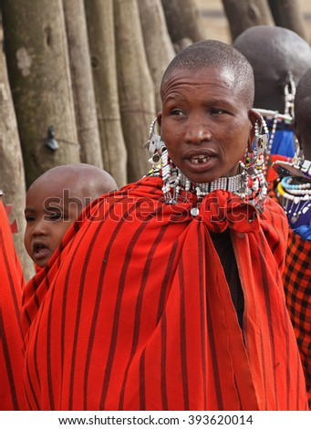 Photo taken at Nogorongoro, Tanzania on October 8, 2015. Portrait of unidentified Masai woman and baby with traditional beaded decorations and colorful garments in their village in Tanzania.   - stock photo