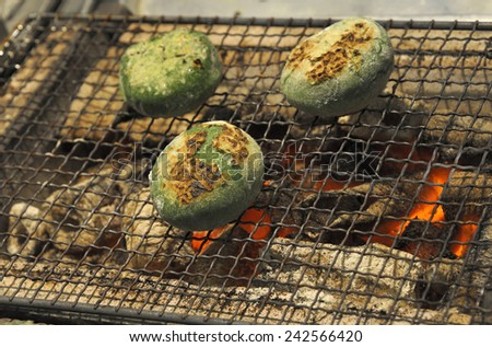 Photo taken in Gion, Kyoto where a seller grills sweet snacks for takwaway.Selective focus at first snack. - stock photo