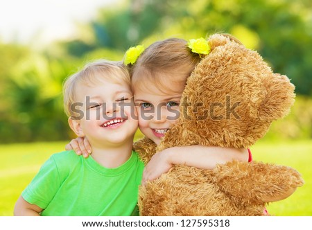 Photo two cute child hugging outdoors, brother and sister having fun on backyard in spring, nice little girl with adorable boy playing with big soft bear toy, best friends, happy childhood concept - stock photo