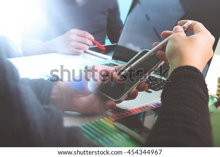 Photo website graphic designer hand working with new project modern studio.Modern laptop digital tablet smart phone on wood table.Books papers documents. Blurred background, sun flare effect