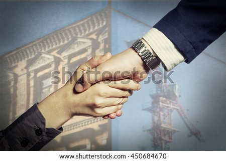 Photo which shows a handshake of two persons (client and contractor), at the conclusion of the deal, on the background of building under construction. - stock photo