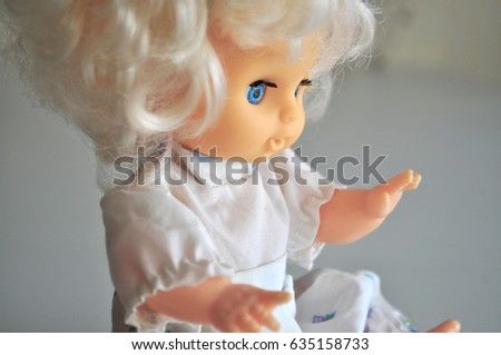 Photo with a pretty little baby-doll with big blue eyes and white curly hair