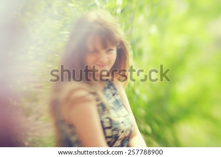 photo with artistic blurring and blur effect. special defocused effect. vintage toning. film retro style. outdoor portrait of a young beautiful woman - stock photo
