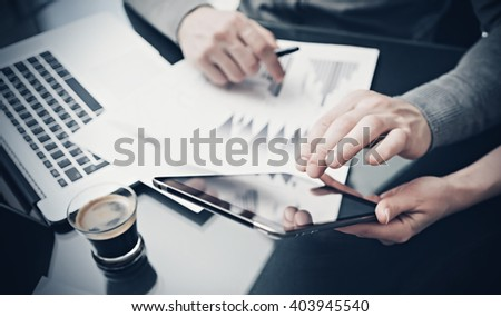 Photo woman showing business reports modern tablet. Statistics graphics on the screen. Banker holding pen for signs documents and touching gadget. Discussion startup idea. Horizontal.Film effect