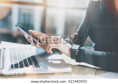 Photo Woman Working Modern loft,Wearing Generic Design Smart Watch.Female Hands Touching screen Mobile Phone.Manager Work Process.Laptop on the wood Table.Horizontal,Burred background. Film effects.