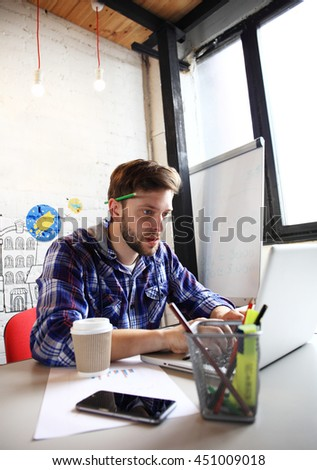 Photo young and talente finance manager working with new project. Handsome man working from his home office. Analyze business plans on laptop. Blurred background, film effect