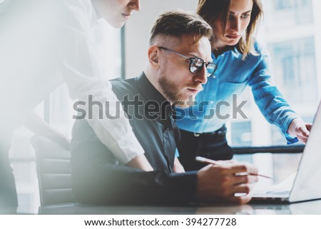 Photo young coworkers team working with new startup project in modern loft. Pencil holding hands, laptop, analyze plans. Horizontal, film effect, blurred background - stock photo