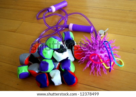 Photograph featuring a purple novelty childrens ball, a colorful whistle, juggling balls and a skipping rope (Australia). - stock photo