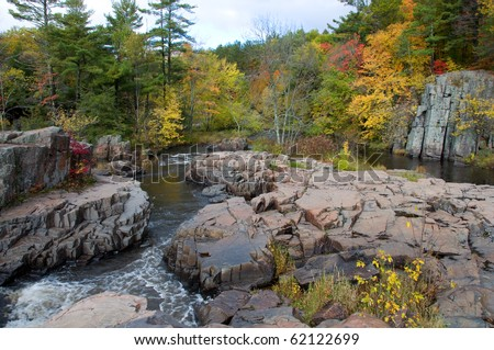 Photograph of a beautiful waterfall area with rock outcroppings, taken during the peak of the autumn colors, with rushing waters and vibrant colors.  Taken in northern Wisconsin. - stock photo