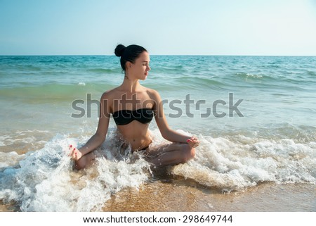 Photograph of a beautiful woman relaxing and meditating on a beach in the waves of the sea. Enjoy life.  Room for text. - stock photo