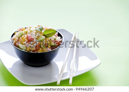 Photograph of a bowl of rice salad with corn tomato and cucumber