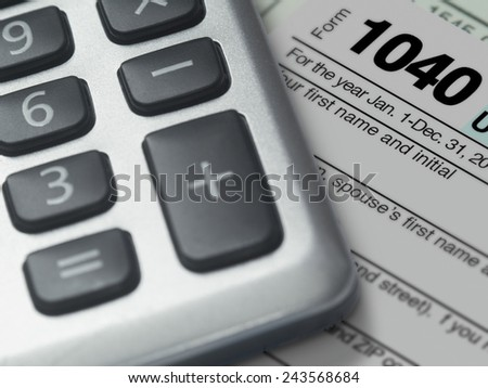 Photograph of a calculator and IRS 1040 form in close up. - stock photo