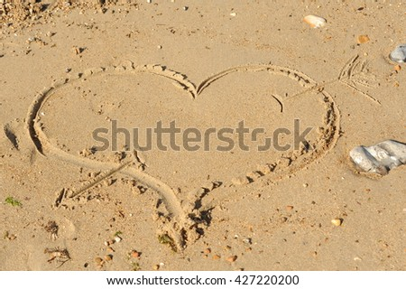 photograph of a cupid heart and arrow drawn in the sand
