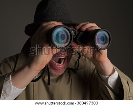 Photograph of a man in trench coat and hat looking through binoculars with huge, cartoonish eyes seen in the lenses. - stock photo