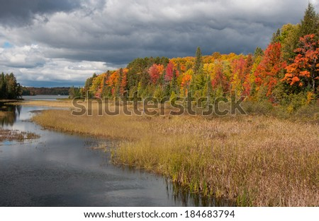 Photograph of a northwoods lake amidst crisp autumn colors brightened by a splash of sunshine while stormy clouds move in. - stock photo