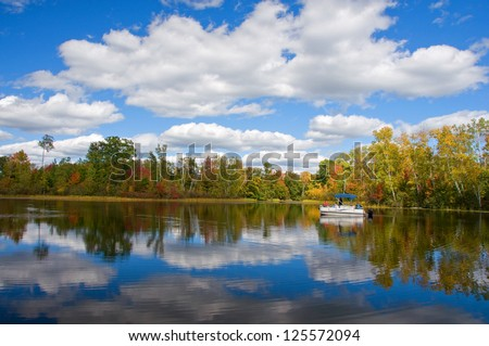 Photograph of a quiet and remote northwoods lake on a beautiful autumn day with clouds reflected in the still blue waters while a pontoon boat of sightseers slowly motors by. - stock photo