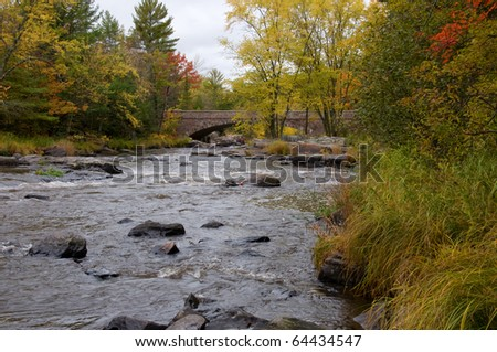 Photograph of a rushing river heading for a falls, looking downstream towards an old historical stone bridge, in the midst of the beauty of the changing colors of autumn in Wisconsin. - stock photo