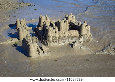photograph of a sand castle collapsing by the tide on the coast of Brittany - stock photo