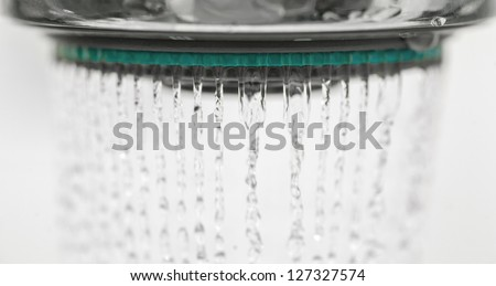 Photograph of a shower head water drops with bokhe sparkles and streams of water. - stock photo