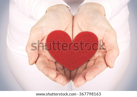 Photograph of a woman's hands holding a heart fabric. Greeting card for Valentine's Day. Stock photography.