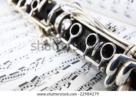 Photograph of a wooden clarinet over some music. - stock photo