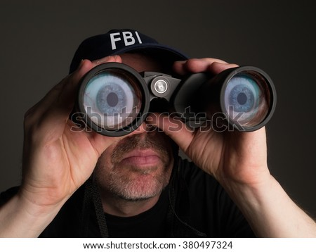 Photograph of an FBI agent in t shirt and baseball cap looking through binoculars with large, cartoonish eyes in the lenses. - stock photo