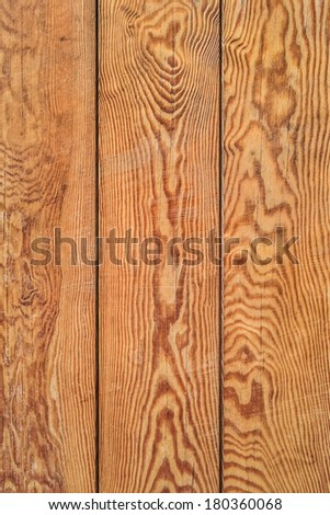 Photograph of bench seat, made of stained and varnished old weathered White pine planks, with conspicuous annual growth lines and dark wood knots. - stock photo