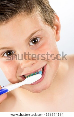 photograph of portrait of a boy brushing his teeth - stock photo