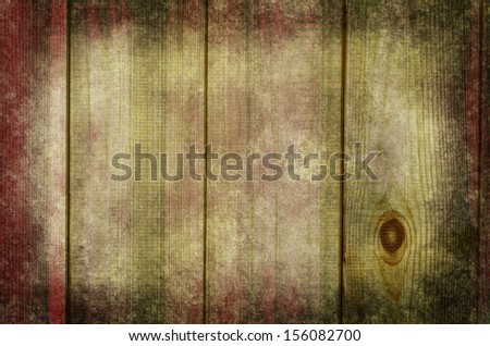 Photograph of raw wood planking, processed to give a weathered,  grungy and rustic appearance with a blend of dark red, green and white hues.  Darker edges give a sense of a border or frame. - stock photo